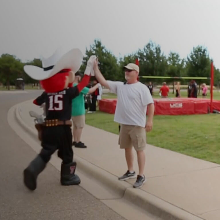 Raider Red giving a crew member a high five while on the set of the Texas Tech University National Ad